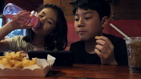 Happy asian child watching on mobile phone and enjoy eating potato fires, Slow motion of brother and sister at restaurant. stock footage