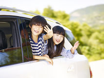 Happy asian children on a sightseeing trip. Happy asian children sticking heads out of rear window of a car and waving hands stock photography