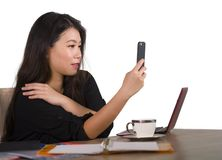 Happy Asian Chinese business woman taking selfie photo with mobile phone at corporate company office desk smiling playful in femal royalty free stock photos