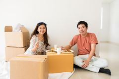 Happy couple eat noodle on carboard box at new house. Happy Asian Chinese couple sitting on floor and eating roasted duck egg noodle on cardboard moving boxes at Stock Photography