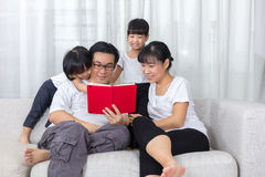 Happy Asian Chinese family reading book on the couch Royalty Free Stock Photo