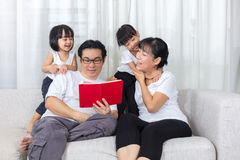 Happy Asian Chinese family reading book on the couch Royalty Free Stock Images