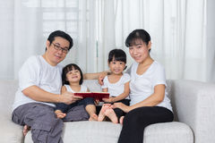 Happy Asian Chinese family reading book on the couch Stock Photography