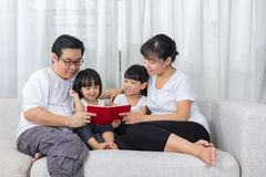 Happy Asian Chinese family reading book on the couch Stock Image