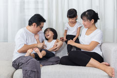 Happy Asian Chinese family sitting on the couch at home Royalty Free Stock Images