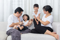Happy Asian Chinese family sitting on the couch at home. Happy Asian Chinese family sitting on the couch in the living room at home royalty free stock image
