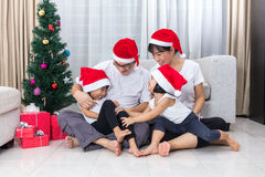 Happy Asian Chinese family sitting on the floor celebrating Christmas. In the living room at home with Santa Claus Hat stock photo