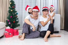 Happy Asian Chinese family sitting on the floor celebrating Chri Royalty Free Stock Photo