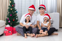 Happy Asian Chinese family sitting on the floor celebrating Chri Stock Photos