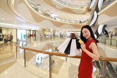 Happy Asian Chinese fashionable woman shopping bags in a mall store casual buyer smile laugh consumption on sale promotion VIP. There is a Asian Chinese modern stock photos