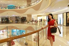 Happy Asian Chinese fashionable woman shopping bags in a mall store casual buyer smile laugh consumption on sale promotion VIP. There is a Asian Chinese modern stock photography