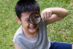 Happy Asian Chinese little boy looking through magnifying glass Royalty Free Stock Photos