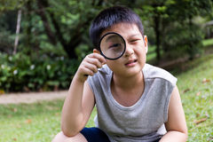 Happy Asian Chinese little boy looking through magnifying glass Stock Images