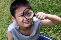 Happy Asian Chinese little boy looking through magnifying glass Stock Photo
