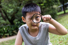 Happy Asian Chinese little boy looking through magnifying glass Royalty Free Stock Image