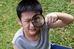 Happy Asian Chinese little boy looking through magnifying glass Stock Image