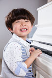 Happy Asian Chinese little boy playing piano at home Stock Photography
