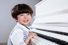 Happy Asian Chinese little boy playing piano at home. Happy Asian Chinese little boy playing piano in the living room at home Royalty Free Stock Images