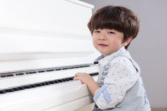 Happy Asian Chinese little boy playing piano at home Royalty Free Stock Photography