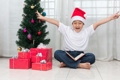 Happy Asian Chinese little boy reading book beside Christmas pre Stock Image