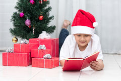 Happy Asian Chinese little boy reading book beside Christmas pre Royalty Free Stock Photo