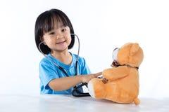 Happy Asian Chinese little doctor girl examine teddy bear Stock Photos