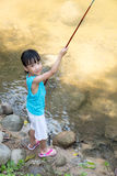 Happy Asian Chinese little girl angling with fishing rod. At the river shore Stock Photos