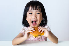 Happy Asian Chinese little girl Eating Burger. Asian Chinese little girl Eating Burger indoor with isolated clean background Royalty Free Stock Photography