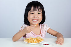 Happy Asian Chinese little girl Eating French Fries Royalty Free Stock Photos