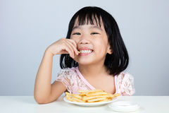 Happy Asian Chinese little girl Eating French Fries Royalty Free Stock Photo