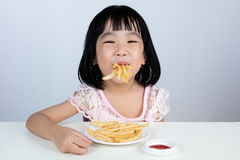 Happy Asian Chinese little girl Eating French Fries Royalty Free Stock Images