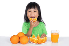 Happy Asian Chinese little girl eating orange Royalty Free Stock Image