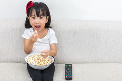 Happy Asian Chinese little girl eating popcorn on the sofa Royalty Free Stock Photography