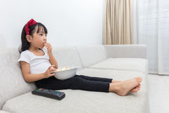 Happy Asian Chinese little girl eating popcorn on the sofa Stock Photo
