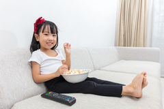 Happy Asian Chinese little girl eating popcorn on the sofa Stock Image