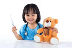 Happy Asian Chinese little girl examine teddy bear with thermome Stock Images
