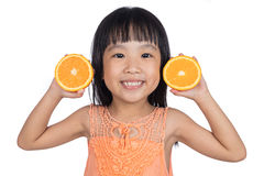 Happy Asian Chinese little girl holding orange Stock Photography