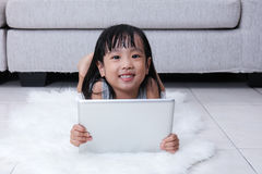 Happy Asian Chinese little girl holding tablet on the floor. In the living room at home royalty free stock photography