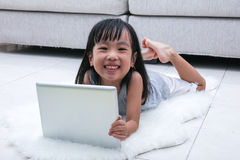 Happy Asian Chinese little girl holding tablet on the floor Royalty Free Stock Image