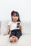 Happy Asian Chinese little girl holding a TV remote control Royalty Free Stock Photos