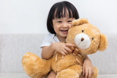 Happy Asian Chinese little girl hugging a teddy bear Royalty Free Stock Photography