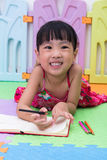 Happy Asian Chinese little girl laying on the floor coloring Stock Images