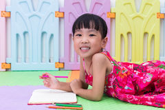 Happy Asian Chinese little girl laying on the floor coloring Royalty Free Stock Image