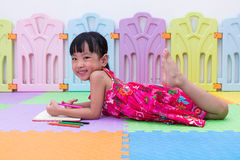 Happy Asian Chinese little girl laying on the floor coloring Stock Photos