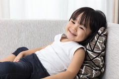 Happy Asian Chinese little girl lying down on the sofa. In the living room at home Stock Photos