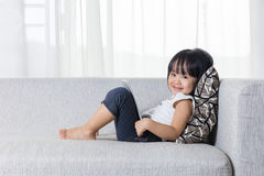 Happy Asian Chinese little girl lying on the sofa with tablet. In the living room at home Stock Photo