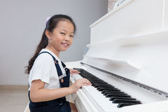 Happy Asian Chinese little girl playing classical piano at home. Happy Asian Chinese little girl playing classical piano in the living room at home Stock Photo