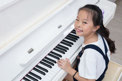 Happy Asian Chinese little girl playing classical piano at home. Happy Asian Chinese little girl playing classical piano in the living room at home Stock Images