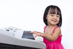 Happy Asian Chinese little girl playing electric piano keyboard Royalty Free Stock Photography