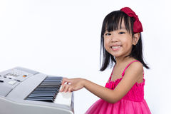 Happy Asian Chinese little girl playing electric piano keyboard. Asian Chinese little girl playing electric piano keyboard in isolated white background royalty free stock image